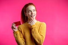 Belle femme heureuse de gingembre jugeant la carte de crédit d'isolement sur la goupille images libres de droits