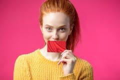 Belle femme heureuse de gingembre jugeant la carte de crédit d'isolement sur le fond rose photo libre de droits