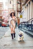 Belle femme heureuse marchant avec un chien à la rue de New York City Images stock