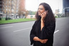 Belle femme heureuse marchant et écrivant ou lisant des messages de sms photographie stock libre de droits