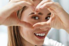 Belle femme heureuse montrant le signe d'amour près des yeux images stock