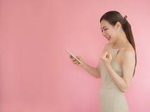 Belle femme heureuse quand téléphone intelligent d'utilisation, moblie asiatique d'utilisation de fille Photographie stock libre de droits