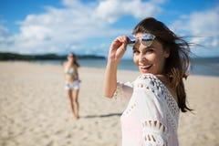 Belle femme heureuse se tenant sur la plage avec rire d'ami Image libre de droits