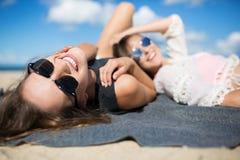 Belle femme heureuse se trouvant sur la couverture sur la plage avec l'ami Photo libre de droits