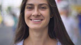 Belle femme heureuse souriant avec des dents et regardant l'appareil-photo, se tenant sur la rue urbaine, dehors banque de vidéos