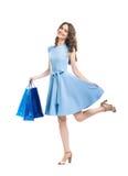 Belle femme heureuse tenant l'isolat coloré de beaucoup de paniers Photo stock