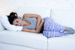 Belle femme hispanique dans l'expression douloureuse tenant la douleur de souffrance de période menstruelle de ventre Photos stock