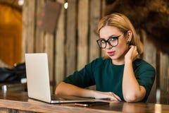 Belle femme intelligente d'affaires s'asseyant à la table au poste de travail avec l'ordinateur portable photos libres de droits