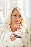 Belle femme intriguée regardant la TV utilisant à télécommande Photos libres de droits
