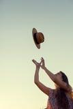 Belle femme jetant son chapeau dans le ciel Image stock