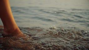 Belle femme jouant dans l'océan au coucher du soleil d'or rêveur banque de vidéos