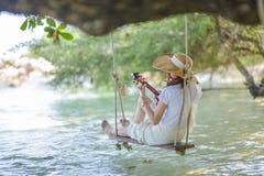 Belle femme jouant l'ukulélé par la mer images stock