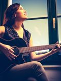 Belle femme jouant la guitare par la fenêtre Photographie stock libre de droits