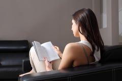 Belle femme à la maison s'asseyant sur un divan affichant un livre Photos stock