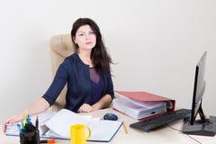 Belle femme lasse au bureau fonctionnant avec des papiers Photographie stock libre de droits