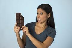 Belle femme latine avec la barre de chocolat se sentant coupable après avoir mordu sur le fond bleu dans le sucre et l'abus doux images stock