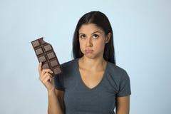 Belle femme latine avec la barre de chocolat se sentant coupable après avoir mordu sur le fond bleu dans le sucre et l'abus doux photographie stock libre de droits