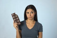 Belle femme latine avec la barre de chocolat se sentant coupable après avoir mordu sur le fond bleu dans le sucre et l'abus doux image stock