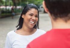 Belle femme latine indigène parlant avec l'ami caucasien Photos stock