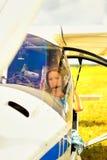 Belle femme le pilote dans un habitacle de l'avion ultra-léger Images stock