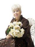 Belle femme mûre blonde avec un bouquet des fleurs Images stock