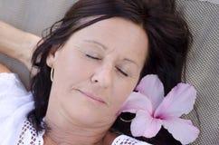 Femme mûre de sommeil avec la fleur Images libres de droits