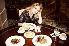 Belle femme mangeant dans une salle à manger photo stock