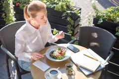 Belle femme mangeant de la salade sur la terrasse de restaurant Images libres de droits
