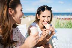 Belle femme mangeant la crème glacée dehors avec son laughin d'ami Photographie stock libre de droits