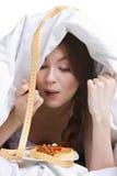 Belle femme mangeant sous le cache Image libre de droits