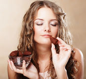 Belle femme mangeant un bonbon de chocolat Photos stock