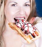 Belle femme mangeant une gaufre avec la glace Photographie stock libre de droits