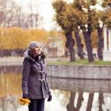 Belle femme marchant en stationnement Fille au-dessus de fond saisonnier d'automne Photographie stock