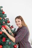 Belle femme mettant un arc dans l'arbre de Noël Photographie stock libre de droits