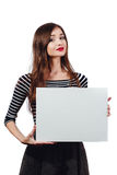 Belle femme mignonne aux cheveux longs de brune tenant une vide-affiche rectangulaire toile blanche avec l'espace pour le texte L Photographie stock