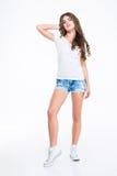 Belle femme mignonne dans le T-shirt, les shorts de jeans et des espadrilles Photographie stock