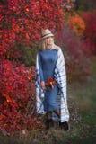 Belle femme mignonne de dame de fille avec les cheveux blonds dans la robe élégante avec le chapeau se tenant dans la forêt d'aut image stock