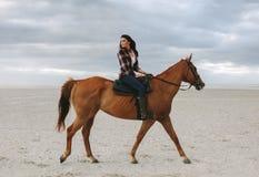 Belle femme montant un cheval dans la soirée photo libre de droits