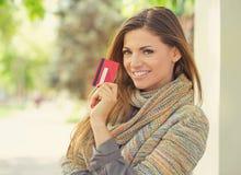 Belle femme montrant la nouvelle carte de crédit photographie stock