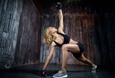 Belle femme musculaire faisant l'exercice sur un fond gris Photographie stock
