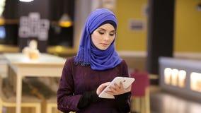 Belle femme musulmane avec le comprimé électronique dans des ses mains, dans le lobby d'hôtel banque de vidéos