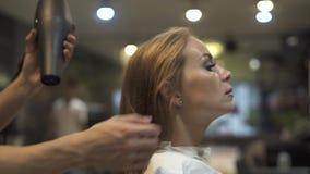 Belle femme obtenant des cheveux de séchage avec le dessiccateur après lavage de la tête dans le salon de beauté Styliste en coif clips vidéos