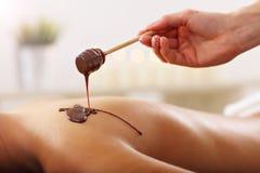 Belle femme obtenant le massage de chocolat dans la station thermale Images stock