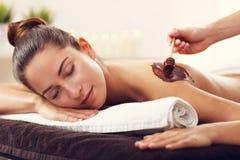 Belle femme obtenant le massage de chocolat dans la station thermale Photo stock