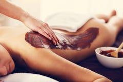Belle femme obtenant le massage de chocolat dans la station thermale Image libre de droits