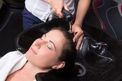 Belle femme obtenant un lavage de cheveux dans le salon de beauté Image libre de droits