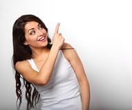 Belle femme occasionnelle de sourire enthousiaste dirigeant le doigt vers le haut de l' Photographie stock