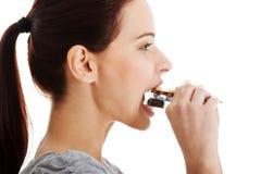 Belle femme occasionnelle essayant de manger la boursouflure des pilules. photographie stock