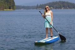 Belle femme paddleboarding sur le lac scénique Photographie stock libre de droits