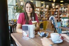 Belle femme parlant à l'ami dans le restaurant Photos stock